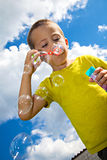 Blowing bubbles. Cute kid blowing soap bubbles Stock Photos