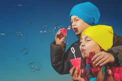 Blowing bubbles. Cute little girl with boy are blowing a soap bubble Royalty Free Stock Photography