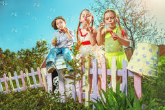 Blowing bubbles. Cute little girls with boy are blowing a soap bubble Royalty Free Stock Image