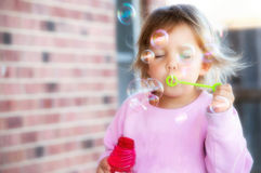 Blowing Bubbles. A little girl blows lots of colorful bubbles outside Stock Photo