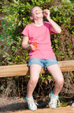 Blowing bubbles outdoors. Girl sitting on fence in park blowing bubbles royalty free stock photos