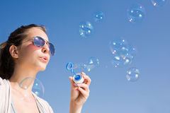 Blowing bubbles into the sky. Stock Photos