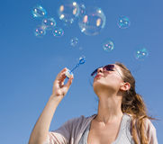 Blowing bubbles into the sky. Beautiful young brunette girl blowing soap bubbles into the sky Royalty Free Stock Photos