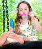 Blowing Bubbles on Tire Swing. Young girl outside blowing bubbles while sitting on tire swing royalty free stock photography