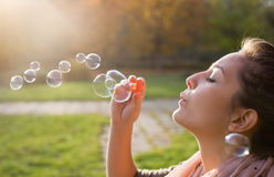 Blowing bubbles into the wind. Stock Photo