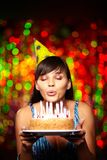 Blowing on candles. Portrait of pretty girl holding birthday cake and blowing candles at party Stock Image