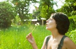Blowing dandelion. Pretty girl blowing a dandelion in a green field stock image