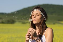 Blowing on a dandelion. Girl blowing on a dandelion outdoor in a sunny day stock photos