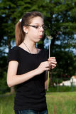 Blowing into dandelion. Teens girl blowing dandelion in the meadow Royalty Free Stock Images