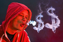 Blowing dollar signs. Hooded man, blowing dollar signs with smoke stock image