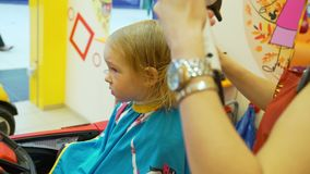 Blowing dry hair of little girl in hair salon. Blowing dry hair of little girl and combing her hair in hair salon stock video footage