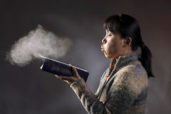 Blowing dust off a book. Stock Images