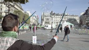 Blowing of giant soap bubble on city square. Paris, France - October 15, 2016: Blowing of giant soap bubble on city square against beautiful baroque building and stock video footage
