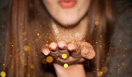 Blowing Glitter. A girl blowing millions of tiny pieces of gold glitter from her hand stock images