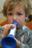 Blowing Hard. A young boy plays a toy trumpet royalty free stock photo
