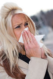 Blowing Her Nose. This young woman sneezing into a tissue either has a cold or really bad allergies Royalty Free Stock Photos