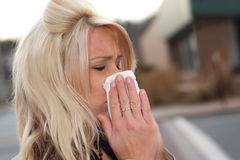 Blowing Her Nose. This young woman sneezing into a tissue either has a cold or really bad allergies Stock Photography