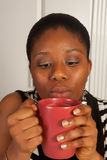 Blowing on hot coffee. Young african woman blowing on her hot coffee cup Royalty Free Stock Photography