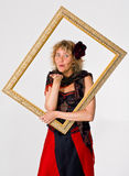 Blowing a kiss. A theatrical actress dressed as a fair lady, blowing a kiss through a wooden frame she is holding Royalty Free Stock Images