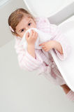 Blowing nose. Little girl blowing nose in bathroom Stock Image