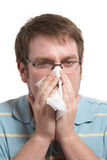 Blowing nose. Sick man with a cold blowing nose on tissue Stock Photography