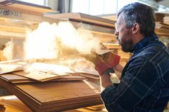 Blowing off sawdust. Serious gray-haired bearded workman in protective goggles blowing sawdust off particleboard while working at warehouse royalty free stock photos