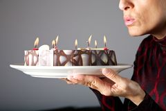 Blowing out small candles on cake Stock Photography