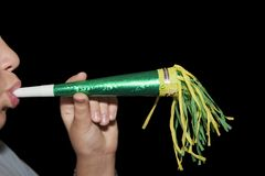 Blowing A Party Horn. A youngster blowing a toy horn with yellow and green tassels at a birthday party -- this could be for any celebration (New Year's, etc stock image