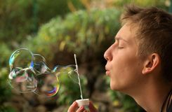 Blowing rainbow bubbles royalty free stock image