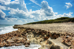 Blowing Rocks Beach & Blue Skies Hobe Sound Florida. Waves crashing over the rocky shoreline of Blowing Rocks Beach in Hobe Sound Florida Royalty Free Stock Images