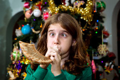 Blowing the Shofar. A young Christian girl blows a Jewish Shofar on Christmas morning. It's a melding of religions and traditions as she stands in front of a Stock Photography
