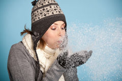 Blowing the snow. Pretty blond girl with winter clothes blowing snow from her hands Royalty Free Stock Photos
