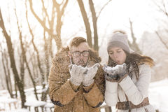 Blowing snow away. Young couple in love having fun on a snowy winter day, blowing snow away Royalty Free Stock Image