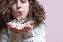 Blowing snowflakes. A woman blowing pretty snowflakes Royalty Free Stock Photos
