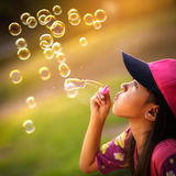 Blowing a soap bubbles. Asian little girl is blowing a soap bubbles Royalty Free Stock Photos