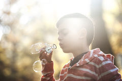 Blowing soap bubbles outdoors Stock Images