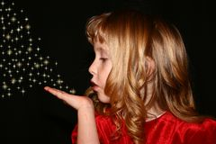 Blowing sparkles. Young girl with curly hair blowing sparkles out of her hand Stock Photography