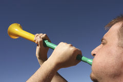 Blowing a vuvuzela royalty free stock photography