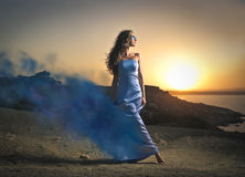 Blowing in the wind. A woman wearing a beautiful light blue dress that fades into the wind Stock Photo