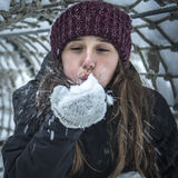 Blowing in winter. Young girl blowing the snow. Love winter Royalty Free Stock Photography