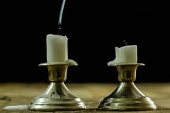 Blown candles in silver candlesticks with smoked wick. Smoke fro. M a wick on a black background. Wooden table royalty free stock photography