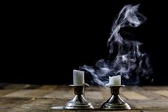 Blown candles in silver candlesticks with smoked wick. Smoke fro. M a wick on a black background. Wooden table stock images