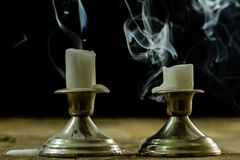 Blown candles in silver candlesticks with smoked wick. Smoke fro. M a wick on a black background. Wooden table stock photos