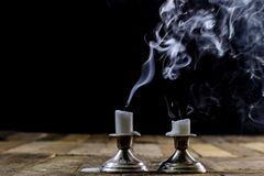 Blown candles in silver candlesticks with smoked wick. Smoke fro. M a wick on a black background. Wooden table royalty free stock photos