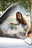 Blown engine. Young woman waiving through the thick smoke coming from the blown engine of her car, looking at the camera stock photography