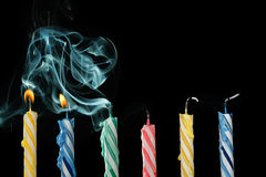 Blown out candles. Birthday candles that have just been blown out with smoke on black background royalty free stock images