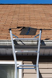 Blown Out Roof Shingles Repair. A ladder set up to repair damaged roof shingles.  A section was blown off after a storm with high winds causing a potential leak Royalty Free Stock Photo