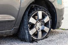 Blown out tire with exploded, shredded and damaged rubber. Destroyed blown out tire with exploded, shredded and damaged rubber on a modern suv automobile. Flat Royalty Free Stock Images