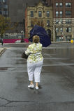 Blown out umbrella. Women holding on to a blown out rain umbrella Royalty Free Stock Images