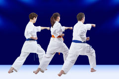 Blows arm adult friends athletes are training on the dark blue background. Blows arm friends athletes are training on the dark blue background Royalty Free Stock Photography